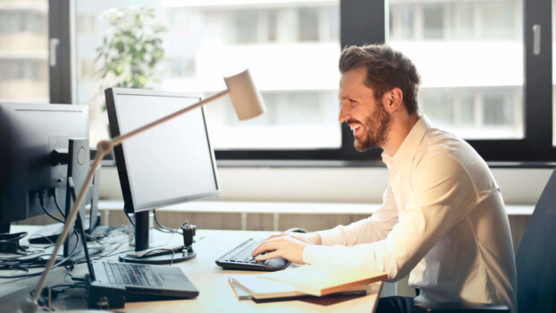 Typ am Schreibtisch ist fröhlich. Symbolbild